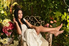 Brunette woman sitting near floral decoration Stock Images