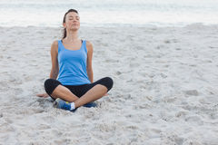 Brunette woman sitting after sport at beach Royalty Free Stock Photography