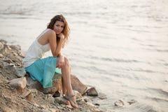 Brunette woman sitting on stone. Beautiful woman wearing blue skirt sitting on stone near water Royalty Free Stock Photography