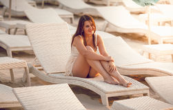 Brunette woman sitting on sunbed on sand beach Royalty Free Stock Images