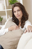 Brunette Woman Sitting Thinking At Home on Sofa Stock Images