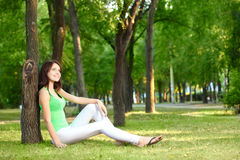 Brunette woman sitting under the tree Royalty Free Stock Photography