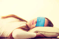 Brunette woman sleeping in blue eye sleep mask Stock Photos