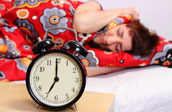 Brunette woman sleeping in her bedroom, ringing alarm clock Royalty Free Stock Photo