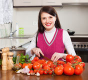 Brunette woman slicing tomatoes Royalty Free Stock Photos