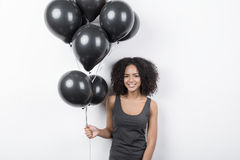 Brunette woman smiling and holding a bunch of black balloons Royalty Free Stock Photo