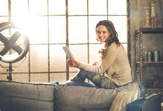 A brunette woman is smiling in a loft living room Stock Photos