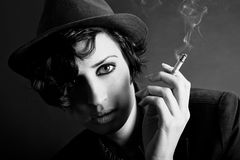 Brunette woman smoking a cigarette on black background wearing a Royalty Free Stock Image