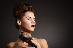 Brunette woman with snail with black eyes and lips. Fashion. Got. Woman with snail with black eyes and lips in Gothic Halloween image royalty free stock image