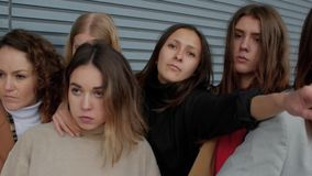 Brunette woman in social danger. Brunette woman sneaks through the crowd against a striped wall. Female students infringe upon a girl. Concepts social danger or stock video footage