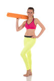 Brunette woman in sports neon yellow leggings and pink bra posing with the orange mat. Royalty Free Stock Photography