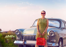 Brunette woman standing near retro car. Beautiful brunette woman standing near retro car Royalty Free Stock Image