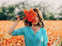 Brunette woman standing with poppies bouquet. Beautiful young woman standing with red poppies bouquet in flower meadow in spring outdoor, looking at camera royalty free stock photography