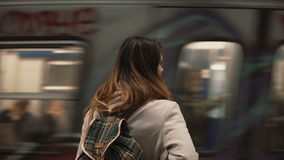Brunette woman standing on railway station and waiting for her train. Girl in underground at evening looks on fast trams. Brunette woman standing on the railway Stock Image