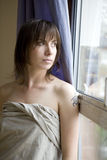 brunette woman standing at window Stock Photography