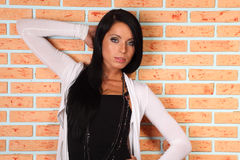 Brunette woman stands near brick wall Royalty Free Stock Images