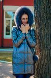 Brunette woman stands under a tree in a park next to a red house. Beautiful slender brunette woman stands under a tree in a park next to a red house in a winter Stock Photos