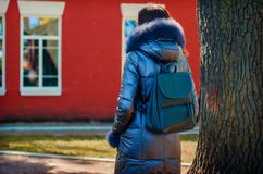 Brunette woman stands under a tree in a park next to a red house. Beautiful woman stands under a tree in a park next to a red house in a winter jacket down Royalty Free Stock Images