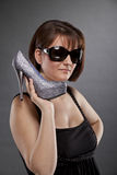 Brunette woman with sunglasses holding a shoe Royalty Free Stock Photography
