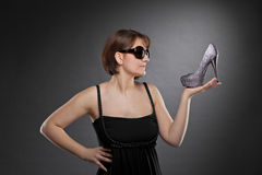 Brunette woman with sunglasses holding a shoe Stock Images