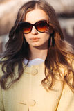 Brunette woman in sunglasses and yellow coat. Stock Photo