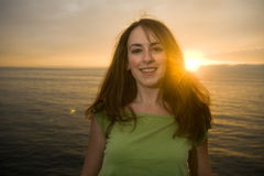 Brunette woman at sunset. Mid twenties brunette female smiles into the camera in front of the ocean at sunset stock photo