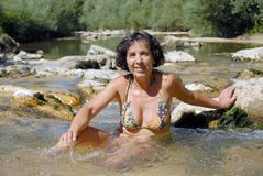Brunette woman in a swimsuit, bathes in the river Royalty Free Stock Photo