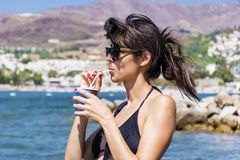 Brunette woman in swimsuit  drinking coffee on the beach Stock Photography