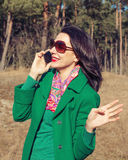 Brunette woman talking on a smartphone in nature Royalty Free Stock Photo