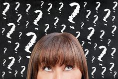 Brunette Woman thinking against blackboard chalkboard question marks. Brunette woman thinking against blackboard or chalkboar full of question marks Royalty Free Stock Photography