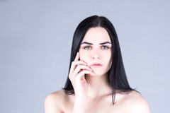 Brunette woman touching her cheek by hand and looking straight. Stock Photos