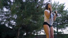 The girl stands under the coniferous trees and training the biceps, slider shooting. Slow motion. A brunette woman is training biceps in the park stock footage