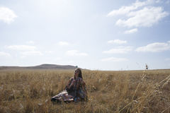 Brunette woman in tribal dress sitting in a field. Color portrait of beautiful brunette woman wearing a colorful tribal dress over boots posing in a field in royalty free stock photography