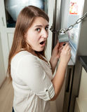 Brunette woman trying to open lock on fridge Royalty Free Stock Photography