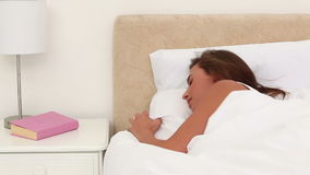 Brunette woman turning off her alarm stock footage