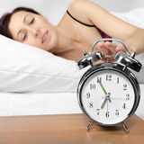 Brunette woman turning off her alarm clock Stock Photography