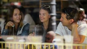 Brunette Woman with Two Friends Sitting at a Cafe, Drinking Some Beverages and Talking. Three Friends are Seen Through. The Window of Restaurant, HD stock video footage