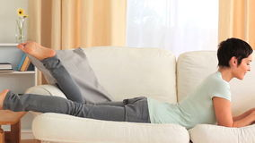 Brunette woman typing on a laptop. While lying on a sofa stock footage
