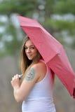 Brunette woman under umbrella in rain Stock Image