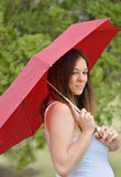 Brunette woman under umbrella in rain Stock Photo