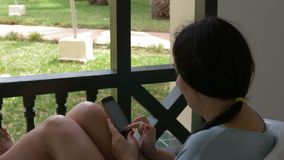 Brunette woman using mobile phone for chat in social networks on outdoor balcony. Woman texting mobile message in smartphone while resting on summer terrace stock footage