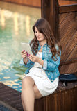 Brunette woman using tablet while sitting on bridge Royalty Free Stock Images