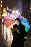 Brunette woman using tablet on the street on rainy Stock Photography