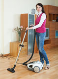 Brunette woman vacuuming  living room Royalty Free Stock Photo