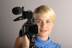 Brunette woman with video camera. Royalty Free Stock Image