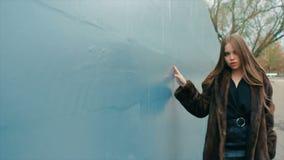 Brunette woman waist coat of brown fur walks along wall slow motion stock video footage