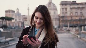 Brunette woman walking in city centre and using smartphone. Girl texting with someone, spending vacation in Rome, Italy. Brunette woman walking in the city stock video footage