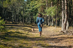 Brunette woman walking through forest Stock Image