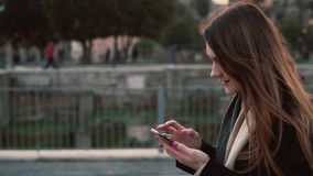 Brunette woman walking in the park and using touchscreen technology at smartphone. Girl spending time outdoors. Brunette woman walking in the park and using stock video