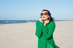 Brunette woman walking by the sea in a green coat Royalty Free Stock Photos